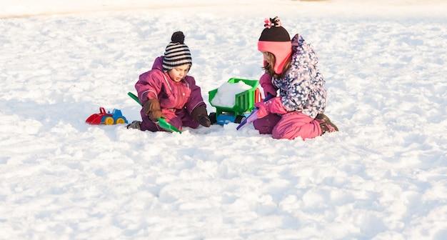 Les enfants jouent avec des voitures et des pelles. concept de nettoyage de la neige de la ville