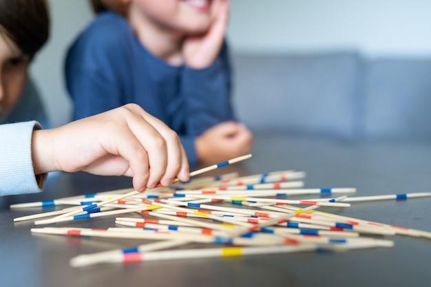 Enfants joyeux jouant au mikado dans le salon à la maison, gros plan. les enfants passent du temps ensemble. week-end en famille. jeu de bâtons en plastique colorés. idées d'activités, jeux à la maison, divertissement d'intérieur.