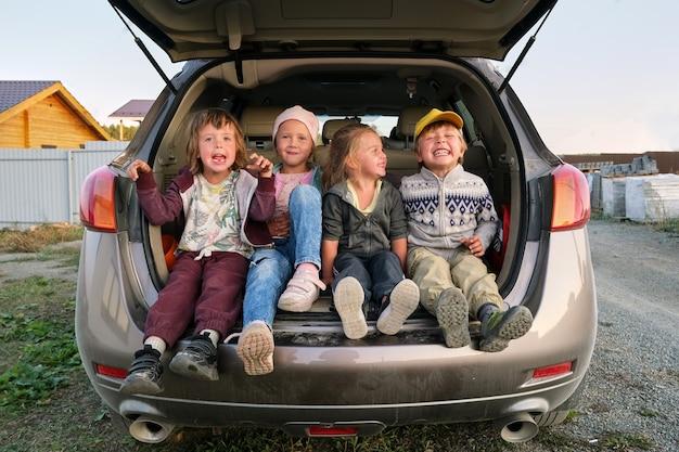 Enfants joyeux s'amusant dans le coffre de la voiture