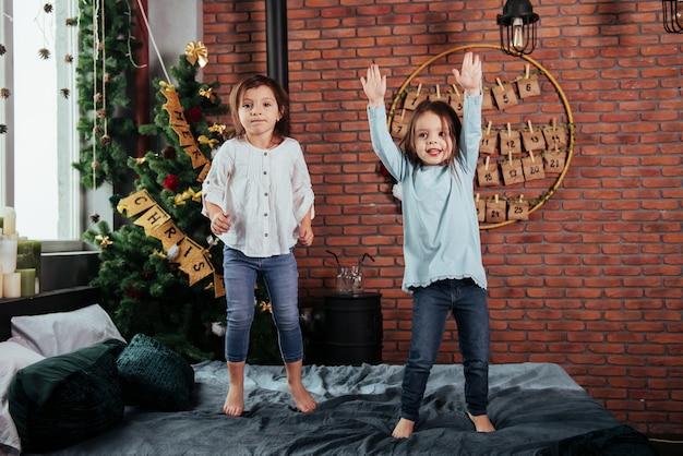 Enfants joyeux s'amusant et sautant sur le lit