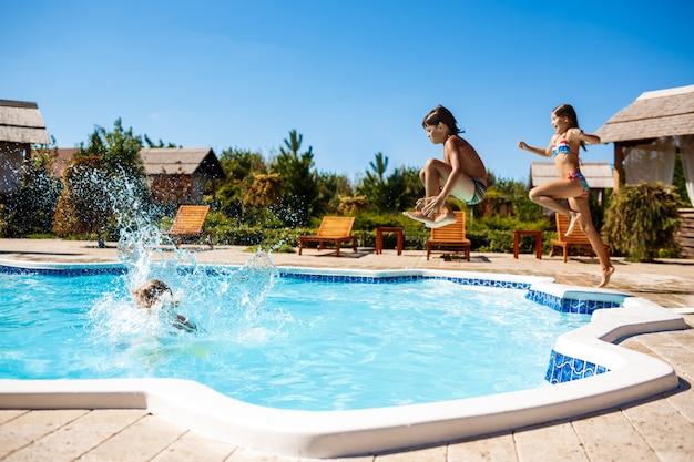 Enfants joyeux se réjouissant, sautant, nageant dans la piscine.