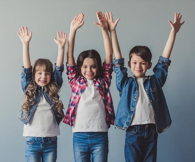 Des enfants joyeux en tenue décontractée lèvent les mains.