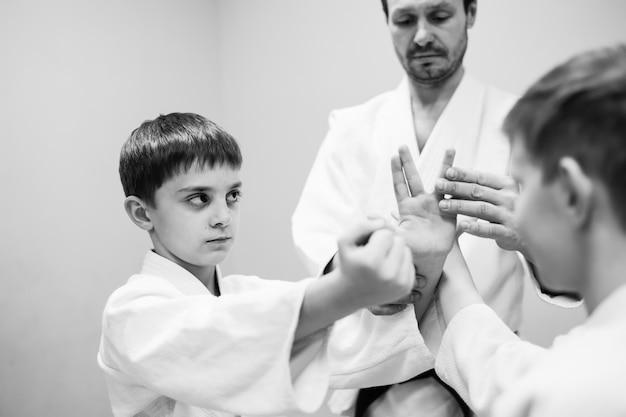 Les enfants en kimono commencent à s'entraîner à l'aïkido.