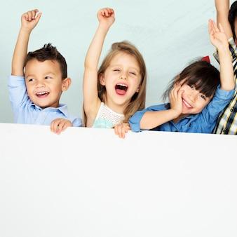 Enfants levant les bras applaudissant avec planche de maquette