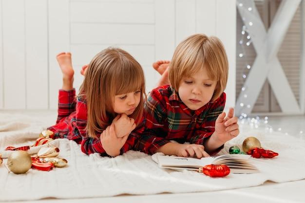 Enfants lisant ensemble le jour de noël