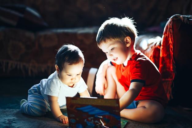 Enfants lisant un livre assis ensemble sur le sol à la maison.