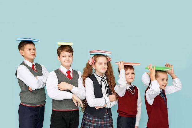 Enfants avec des livres en studio sur fond bleu.