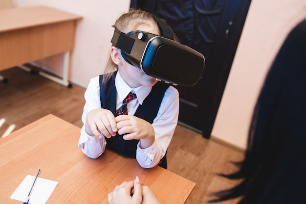 Les enfants avec des lunettes de réalité virtuelle sont au bureau de l'école