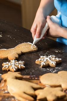 Enfants à la main décorer des biscuits avec du sucre.