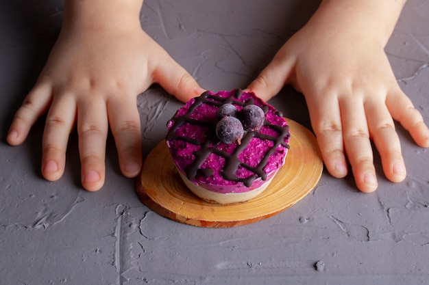 Enfants mains avec un gâteau aux groseilles.