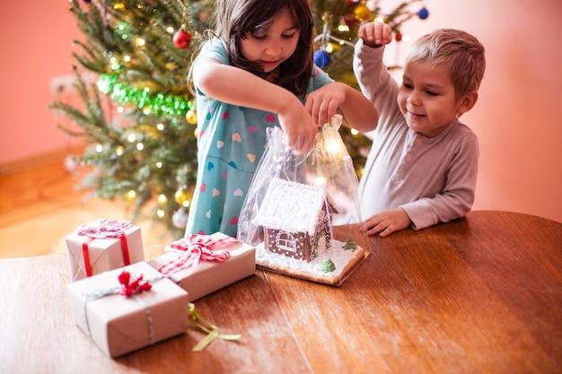 Enfants avec maison de biscuits en pain d'épice au moment de noël