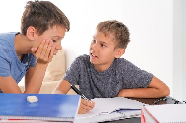 Enfants à la maison faire leurs devoirs avec des livres et parler