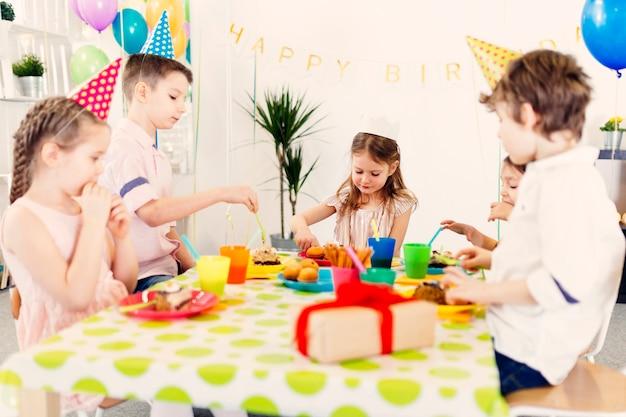 Enfants mangeant des bonbons à table