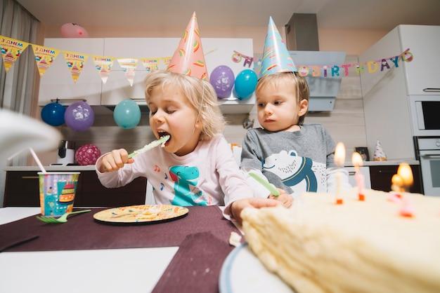 Enfants mangeant le gâteau sur la fête d'anniversaire