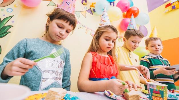 Enfants mangeant un gâteau sur la fête d'anniversaire