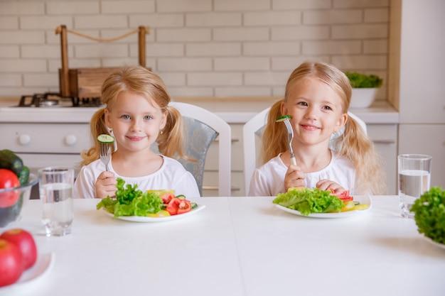 Les enfants mangent des aliments sains dans la cuisine