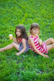 Les enfants mangent des glaces dans le parc.