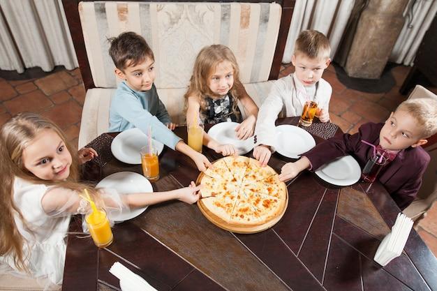 Les enfants mangent une pizza au restaurant.