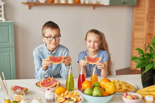 Les enfants mangent des tranches de pastèque à la cuisine