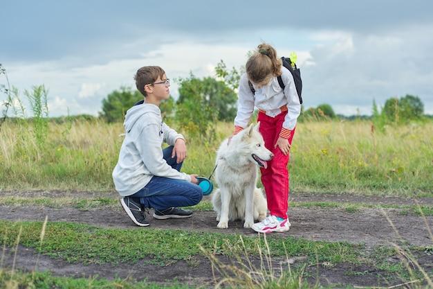 Enfants marchant avec un chien blanc dans le pré le jour de l'automne