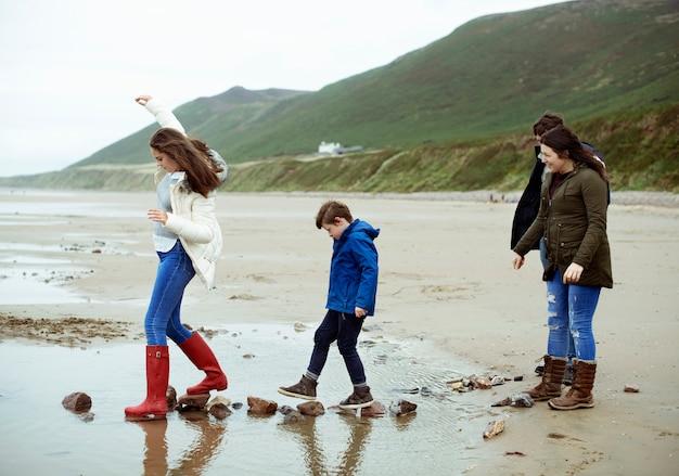 Enfants marchant sur des pierres à la plage