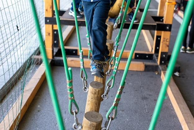Enfants marchant sur des troncs suspendus par des cordes dans un parc d'aventure.