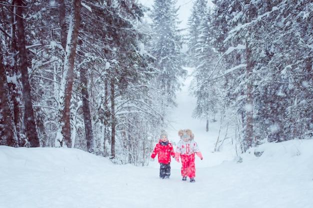 Enfants marchent dans la forêt de neige