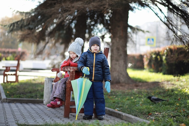 Les enfants marchent dans le parc d'automne à l'automne