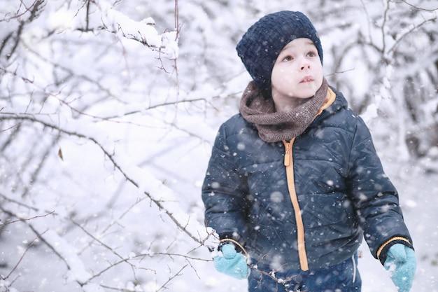 Les enfants marchent dans le parc avec la première neige