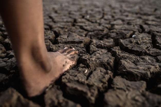 Les enfants marchent pieds nus dans la boue
