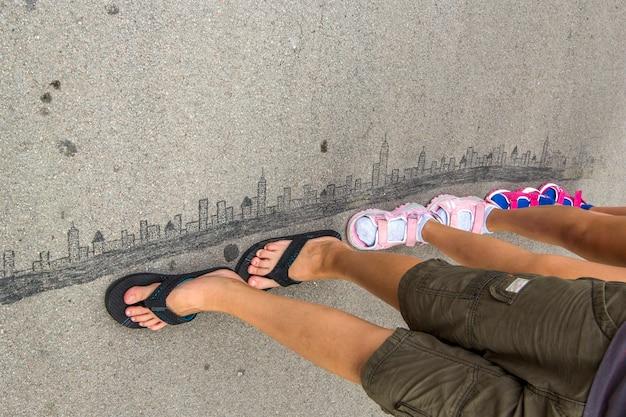 Les enfants marchent sur la ville moderne dessinée sur l'asphalte avec de la craie.