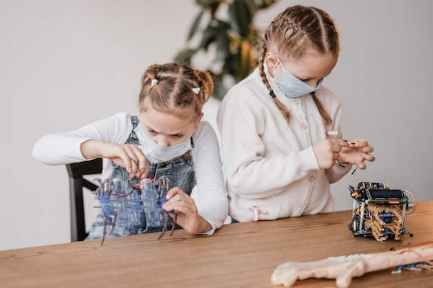 Enfants avec des masques médicaux apprenant à utiliser les composants électriques