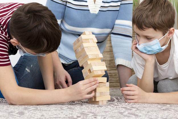 Enfants avec des masques médicaux jouant au jenga avec la mère
