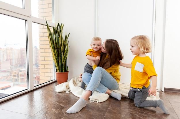 Enfants et mère à angle élevé à la maison