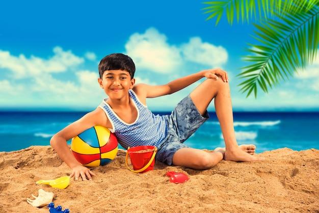 Enfants mignons asiatiques indiens jouant au sable de plage