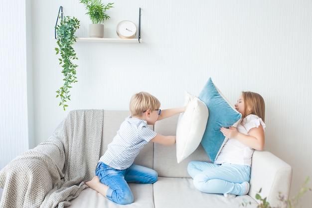 Enfants mignons ayant une bataille d'oreillers