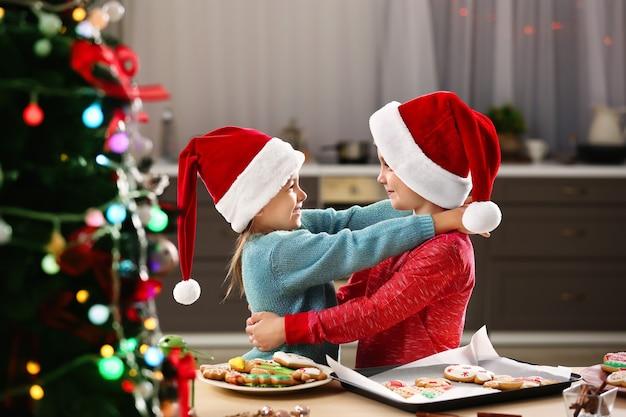 Enfants mignons avec des biscuits de noël dans la cuisine