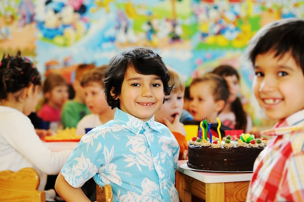 Enfants mignons célébrant la fête d'anniversaire dans la cour de récréation