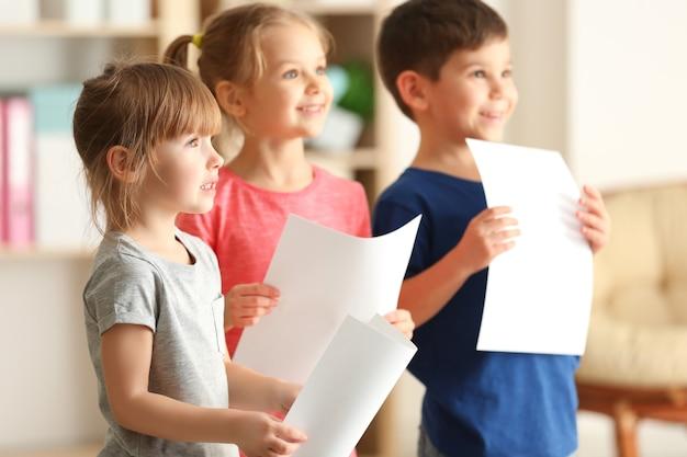 Enfants mignons chantant en classe de musique