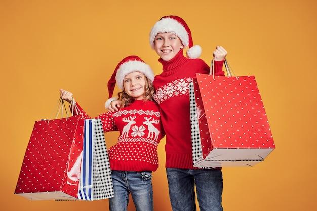 Enfants mignons en chapeaux et chandails de père noël rouge étreignant et tenant des sacs à provisions et ballons dorés sur fond jaune