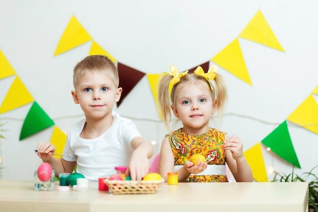 Enfants mignons dans des vêtements colorés, fond jaune festif, les enfants peignent des oeufs de pâques