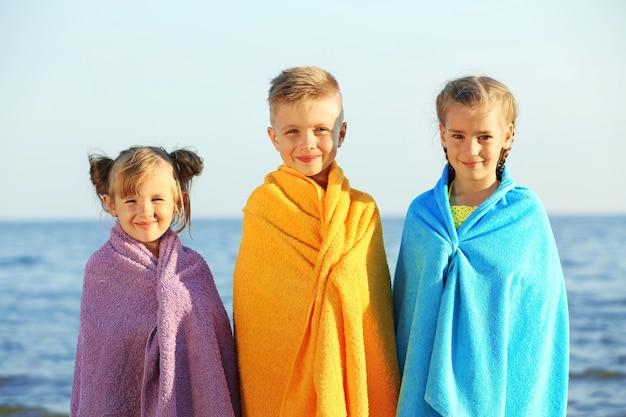 Enfants mignons enveloppés dans une serviette sur la plage