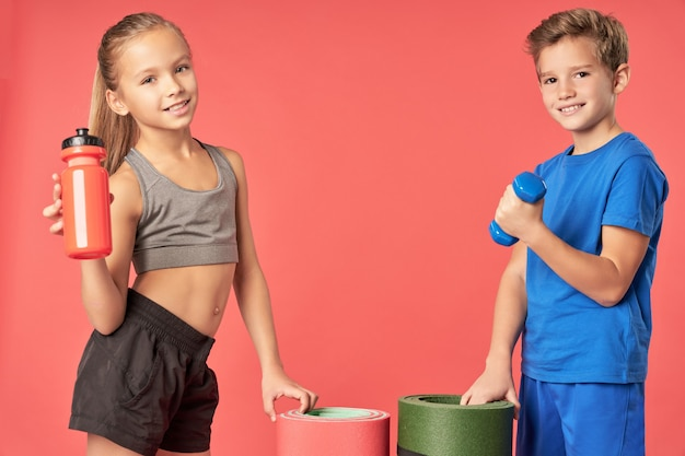 Enfants mignons avec équipement de sport debout sur fond rouge