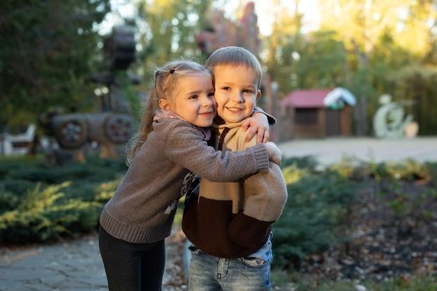 Des enfants mignons, un garçon et une fille jouent, s'assoient et s'embrassent dans le parc en automne.