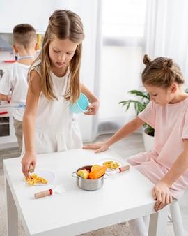 Enfants mignons jouant avec un jeu de cuisine