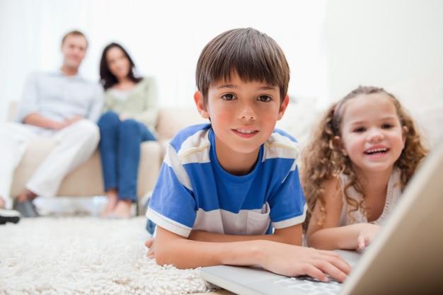 Enfants mignons jouant à des jeux d'ordinateur sur un ordinateur portable