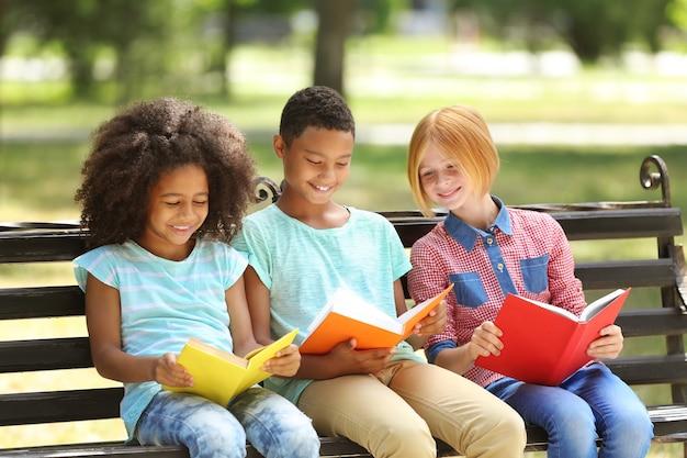 Enfants mignons lisant des livres sur un banc