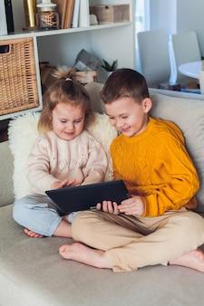Des enfants mignons parlent par appel vidéo à l'aide d'une tablette. quarantaine. une famille. accueil. confortable.