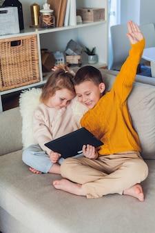 Des enfants mignons parlent par appel vidéo à l'aide d'une tablette. quarantaine. une famille.