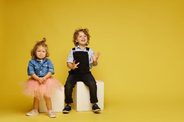 Enfants mignons posant. petite fille triste et garçon heureux en tenues décontractées